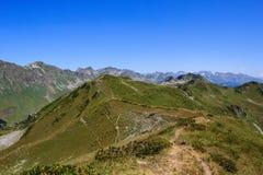 Zandig die voetpad over bergketen met groene alpiene weiden wordt behandeld royalty-vrije stock afbeeldingen