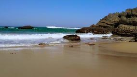 Zandig en rotsachtig strand met golven op de kust van de Atlantische Oceaan in Portugal stock videobeelden