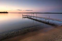 Zandig strand en dok naast meer bij zonsondergang Minnesota, de V royalty-vrije stock afbeelding