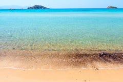 Zandig strand en duidelijk turkoois water Stock Afbeeldingen