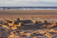 Zandig strand en panorama van overzeese kust tijdens zonsondergang stock foto's