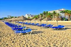 Zandig strand met bedden en zonparaplu's Stock Afbeeldingen