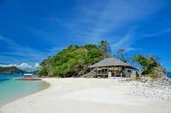 Zandig strand met bungalowwen en een boot dichtbij het Eiland Busuanga Royalty-vrije Stock Foto