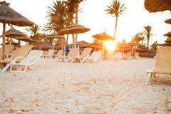 Zandig strand met deckchairs Stock Fotografie