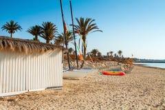 Zandig strand met deckchairs en parasols Stock Foto's