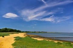 Zandig strand met mening van dorp en kerk over de baai stock afbeeldingen