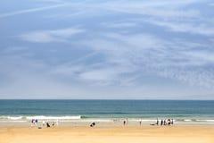 Zandig strand met mensen die gaan surfen Stock Afbeelding