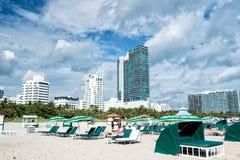 Zandig strand met mensen die op stoelen onder groene paraplu's ontspannen Stock Fotografie