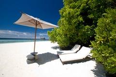 Zandig strand met sunbeds en paraplu Royalty-vrije Stock Afbeeldingen