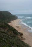 Zandig strand met verpletterende hierboven golven van Stock Foto