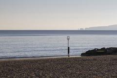 Zandig strand met wazige klippenachtergrond op zonnige de wintersdag Stock Afbeelding