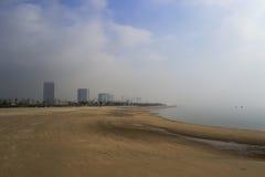 Zandig strand van houtian stad in mist Stock Foto