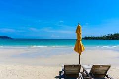 Zandig tropisch strand met ligstoelen Stock Foto's