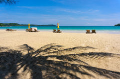 Zandig tropisch strand met ligstoelen Stock Afbeelding