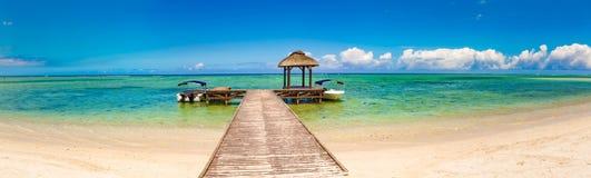Zandig tropisch strand Pier op de voorgrond Panorama stock foto