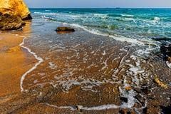 Zandige oceaankust met gele rotsen, overzeese golven met wit schuim Royalty-vrije Stock Fotografie