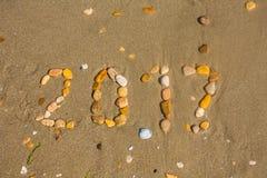 Zandige strandclose-up, de achtergrond van het Zeekustzand Tekst 2017 met stenen wordt gemaakt die Stock Foto