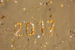 Zandige strandclose-up, de achtergrond van het Zeekustzand Tekst 2017 met stenen wordt gemaakt die Stock Fotografie