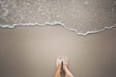 Zandige voeten die door een naderbij komende milde overzeese golf moeten worden gewassen stock foto