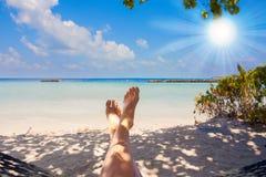 Zandige voeten op het strand met duidelijk oceaanwater onder zon Stock Foto