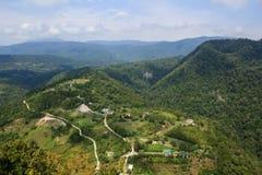 Zandige weg en kleine oude dorpshuizen in de bergen van de Kaukasus royalty-vrije stock foto's
