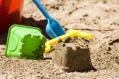 Zandkasteel en stuk speelgoed hulpmiddelen stock afbeeldingen