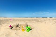 Zandkasteel met speelgoed bij het strand stock foto's