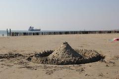 Zandkasteel met vrachtschip op de achtergrond Stock Afbeeldingen