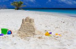 Zandkasteel op strand en jonge geitjesspeelgoed Stock Afbeeldingen