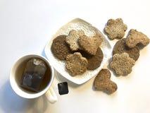 Zandkoekkoekje met sesamzaden op een plaat en een kop thee royalty-vrije stock foto's