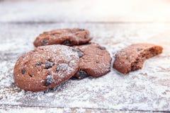 Zandkoekkoekjes met chocoladeschilfers op houten die achtergrond met gepoederde suiker wordt bestrooid Vers gebakje royalty-vrije stock foto