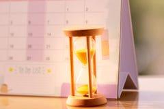 Zandloper die op kalenderconcept voor tijd weg voor belangrijke benoemingsdatum uitglijden stock foto's