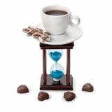 Zandloper en een kop van koffie met snoepjes Stock Fotografie