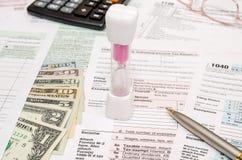 Zandloper met belastingsvorm 1040, calculator, pen en dollar Royalty-vrije Stock Fotografie
