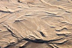 Zandoppervlakte met de hulp door waterstromen die wordt gevormd Stock Foto's