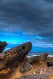 Zandsteenrotsen die uit aan overzees met een het broeden hemel kijken Stock Afbeeldingen