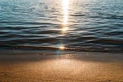 Zandstrand en overzeese golf op achtergrond van de zonsondergang de lichte, rustige zomer royalty-vrije stock afbeelding