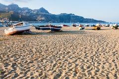 Zandstrand met boten in de stad van Giardini Naxos Stock Foto