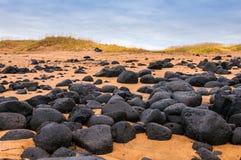 Zandstrand met zwarte rotsen in IJsland - kleine stad op Snaefellsnes-schiereiland stock foto
