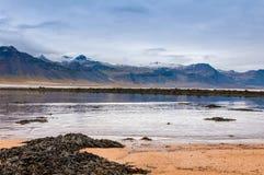 Zandstrand met zwarte rotsen in IJsland - kleine stad op Snaefellsnes-schiereiland stock afbeelding