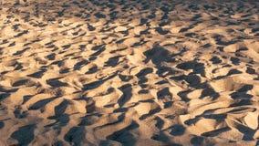 Zandtextuur met schaduwen in zonsonderganglicht Zandig strand als achtergrond royalty-vrije stock fotografie