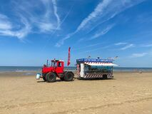 View on red tractor with trailer selling fresh fish products and snacks on beach of dutch north sea in summer
