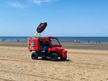 View on red vehicle selling ice cream on beach of dutch north sea in summer
