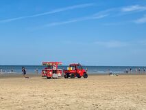 View on red vehicle with trailer selling ice cream on beach of dutch north sea in summer