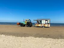 View on tractor with trailer selling snacks and drinks on beach of dutch north sea in summer