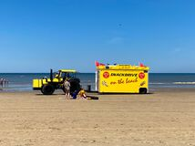View on tractor with yellow trailer selling snacks and drinks on beach of dutch north sea in summer