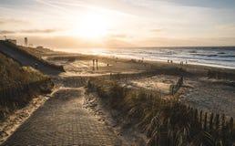 Zandvoort-Strand in den Niederlanden während des Sonnenuntergangs mit den Leuten, die entlang die Küstenlinie gehen Stockfotografie