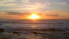 Zangão aéreo disparado no por do sol sobre Oceano Atlântico, movendo-se para trás com as ondas que quebram na praia abaixo video estoque