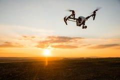 zangão com voo da câmara digital no céu sobre o campo no por do sol foto de stock