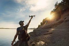 Zangão de lançamento do turista masculino da mão no por do sol bonito na floresta imagem de stock